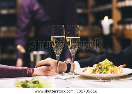 Two champagne glasses on the table with white tablecloth. Shelves with wine and candles are on background.