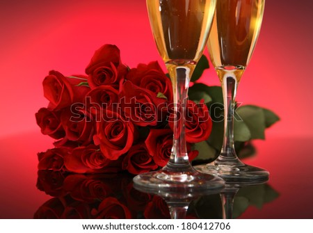two champagne glasses with a dozen red roses in background  - stock photo