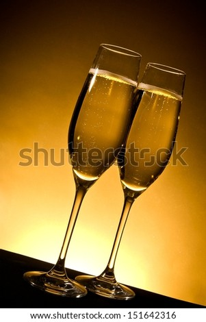 two champagne glasses with bubbles on golden background - stock photo