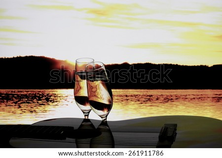 Two champagne glasses with guitar at sunset, close up - stock photo