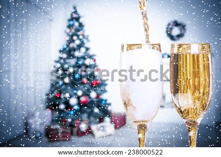 Two Champagne Glasses With Snow On Defocused Background Living Room With Christmas Tree. Blue toned - stock photo