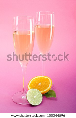 Two champagne or cider glasses with lime and orange slices - stock photo
