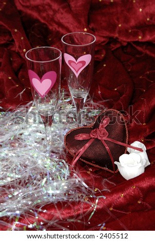 Two champaign glasses and a red heart on red valentine background. - stock photo