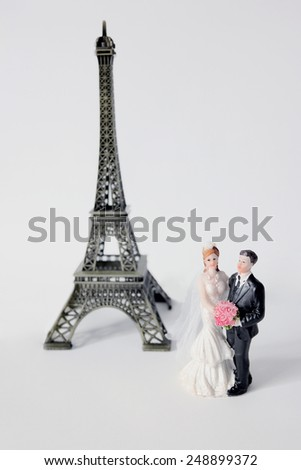 Two characters near a model of eiffel tower in wedding outfits. Honeymoon in Paris, France - stock photo