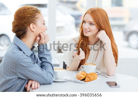 Two charming happy young women drinking coffee and talking in cafe  - stock photo