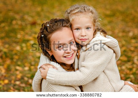 Two charming sisters in the same curly beige knitted sweater embrace on a background of fallen autumn leaves