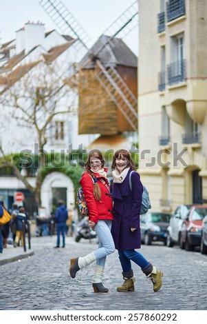 Two cheerful beautiful girls in Paris, having fun on Montmartre - stock photo