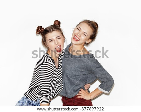 Two cheerful beautiful girls posing for camera inside. Bright makeup, hairdo and casual style. White background, not isolated. 