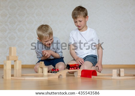 two cheerful blond brother sitting on the floor and playing wooden blocks and train