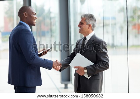 two cheerful businessman handshaking in conference hall - stock photo