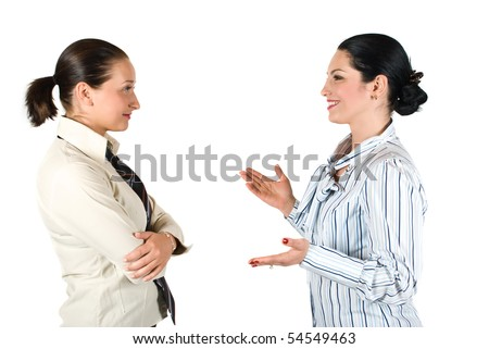 Two cheerful businesswoman have a conversation,the brunette woman explaining something and gesturing with hands while the other listen her very attentive - stock photo