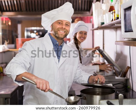 Two cheerful cooks working at take-away restaurant kitchen - stock photo