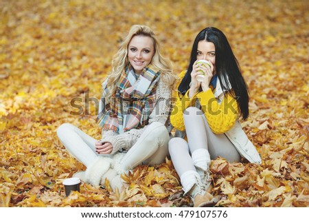 Two cheerful female friends drinking coffee in autumn park