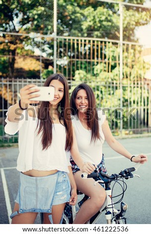 Two cheerful friends enjoying outdoor together and taking selfie photo. Selective focus on second girl.