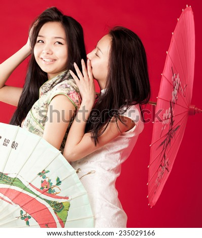 Two cheerful girl-friends Red background - stock photo