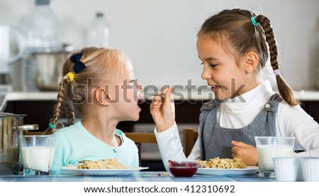 Two cheerful girls eating healthy oatmeal at home kitchen - stock photo