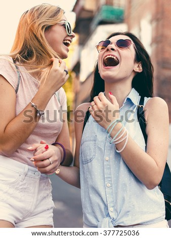 Two cheerful girls in laugh and having fun in city. Film colors. - stock photo