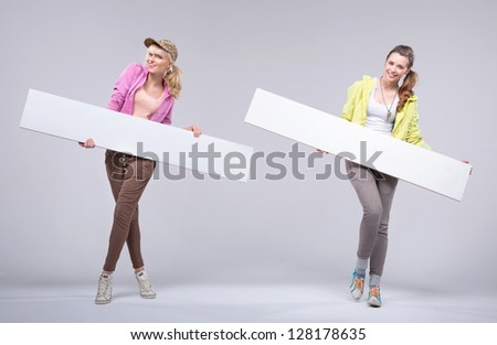 Two cheerful girls showing empty boards