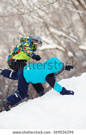 Two cheerful happy boy playing in winter park, outdoor - stock photo