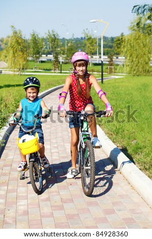 Two cheerful kids riding bikes in park - stock photo