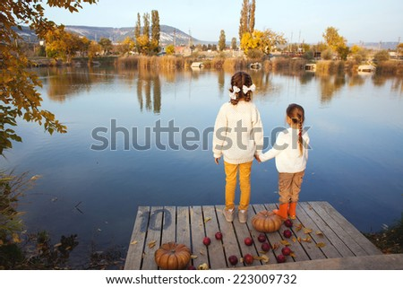 Two cheerful little girls playing on the lake in warm autumn day / Fall lifestyle portrait of children having fun on wooden berth over the river landscape - stock photo