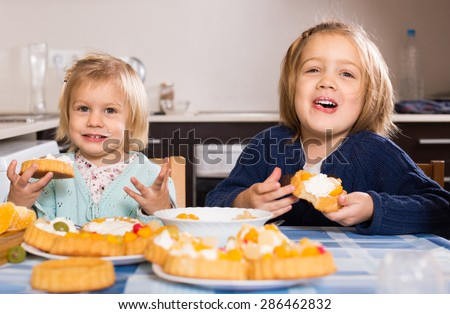 Two cheerful little sisters eating cream desserts at home kitchen