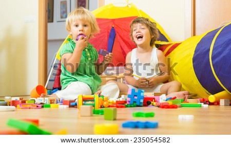 Two cheerful little sisters playing with blocks in home interior  - stock photo