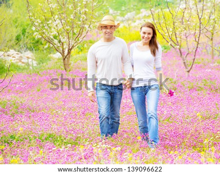 Two cheerful lovers walking in spring garden, having fun outdoors, relaxation on backyard, romance and love concept  - stock photo