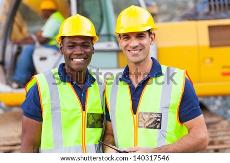 two cheerful male road construction workers on construction site - stock photo