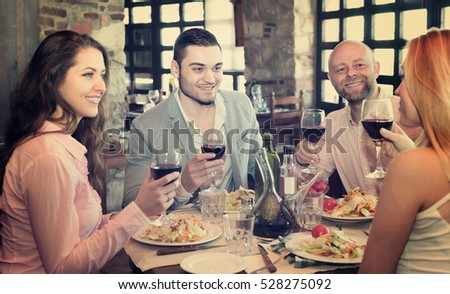 Two cheerful married couple sitting at restaurant table