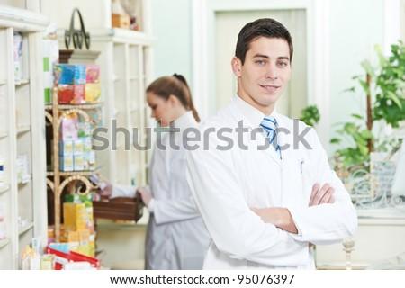 Two cheerful pharmacist chemist  worker standing in pharmacy drugstore - stock photo