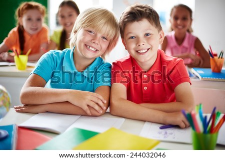 Two cheerful schoolboys looking at camera in classroom - stock photo