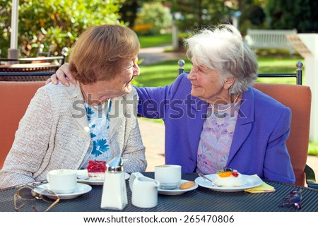 Two Cheerful Senior Best Friends Talking at the Outdoor Table Closely with Coffee and Snacks While One is Holding the Shoulder of the Other. - stock photo