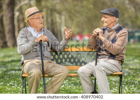 Two cheerful senior gentlemen talking to each other seated on a bench in a park - stock photo