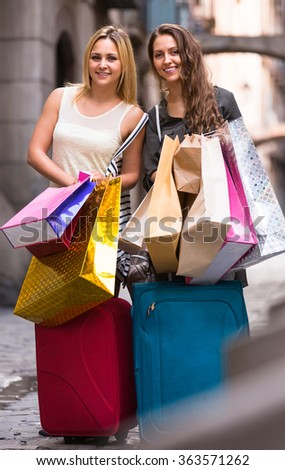 Two cheerful smiling girls with suitcases and shopping bags standing in the street