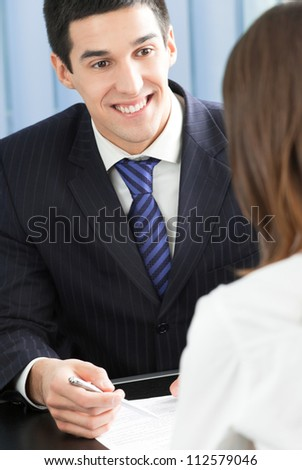 Two cheerful smiling young businesspeople, or business man and client, working at office - stock photo