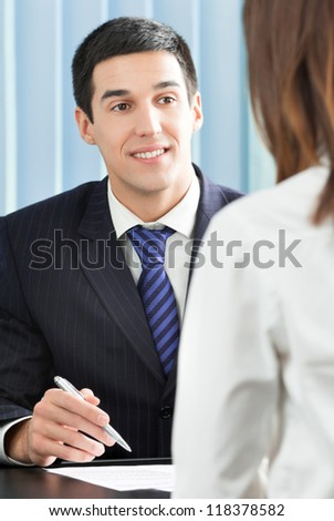 Two cheerful smiling young businesspeople, or business man and client, working at office