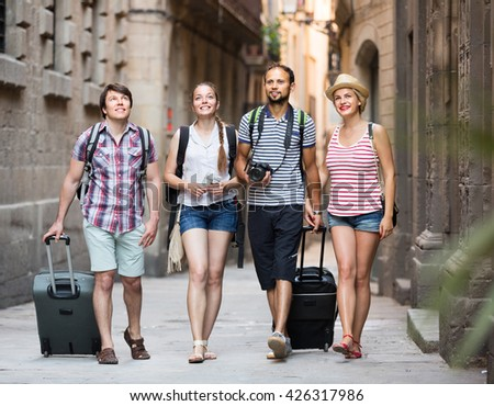 Two cheerful traveler couples with travel bags walking through the city. Selective focus - stock photo