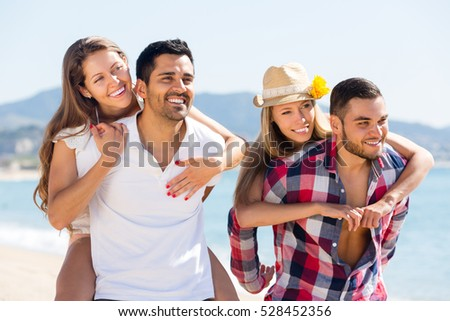 Two cheerful young couples on sandy beach at summer. Selective focus