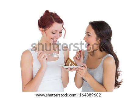 Two cheerful young female friends eating pastry together over white background - stock photo