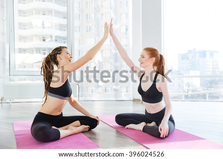 Two cheerful young sportswomen sitting and giving high five after training - stock photo
