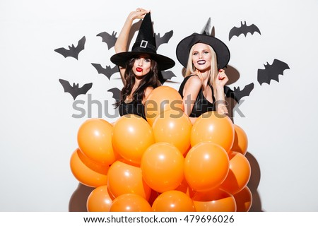 Two cheerful young women in witch halloween costumes dancing with orange balloons over white background