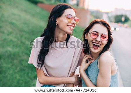 Two cheerful young women walking on the street at sunset. Best friends