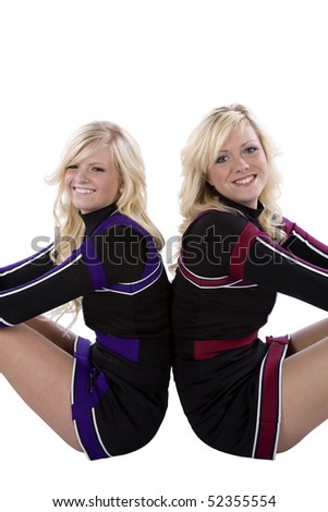 Two cheerleaders sitting on the ground with there backs to each other. - stock photo
