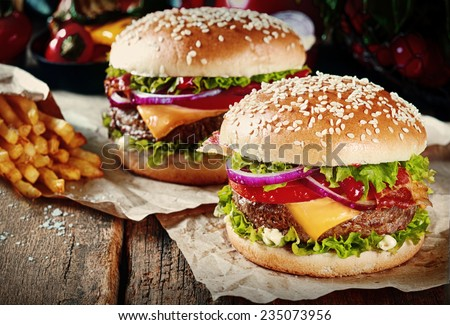 Two cheeseburgers on sesame buns with succulent beef patties and fresh salad ingredients served with French Fries on crumpled brown paper on a rustic wood table - stock photo