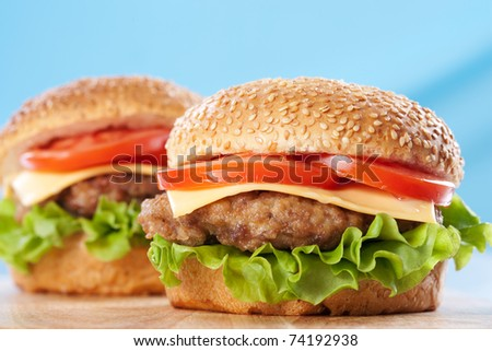 Two cheeseburgers with tomatoes and lettuce on a wooden table with blue background - stock photo