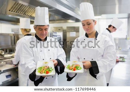 Two Chef's presenting their salmon dishes in the kitchen - stock photo