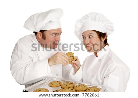 Two chefs fighting over a freshly baked chocolate chip cookie.  Isolated on white. - stock photo
