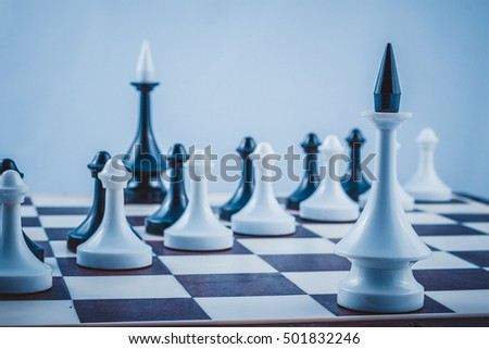 Two chess king and pawns black and white on a chess Board closeup