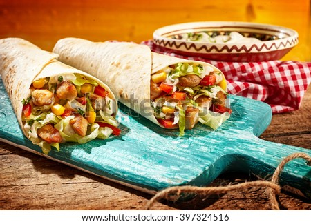 Two Chicken Fajitas Stuffed with Fresh Vegetables Resting on Worn Blue Painted Wooden Cutting Board on Wood Table with Dip Sauce in Tex Mex Mexican Restaurant - stock photo